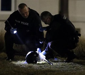 Police shine a light on a helmet as they investigate the scene where two police officers were shot outside the Ferguson Police Department Thursday, March 12, 2015, in Ferguson, Mo. (AP Image)