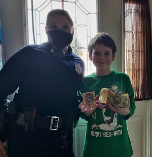 Officer Little poses with an unnamed little boy and the gifts she bought him.