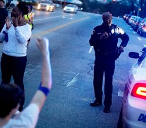 An officer stands watch while standing at an intersection during a protest against the shooting death of Anthony Hill by a police officer, in Decatur, Ga.