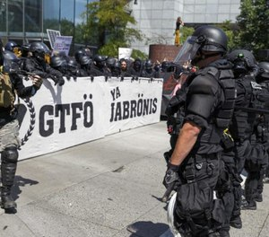 Portland police keep Patriot Prayer affiliates separate from antifa protesters during a rally in Portland, Ore., Saturday, Aug. 4, 2018.