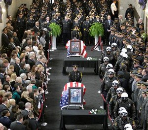 Jamal Knox's rap song's lyrics contained a reference to Richard Poplawski who murdered three Pittsburgh officers in 2009. In this April 8, 2009, file photo family and officials pay their respects to those three Pittsburgh police officers.