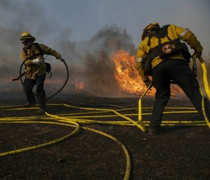 Firefighters work to prevent flames from reaching nearby homes during the Easy Fire in Simi Valley, Calif. (AP Photo/Christian Monterrosa)
