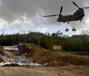 A U.S. Army helicopter transports material to repair the Guajataca Dam, damaged during Hurricane Maria, in Quebradillas, Puerto Rico.