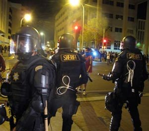 In this March 30, 2014 file photo, riot police stand guard near a crowd protesting police shootings in Albuquerque, N.M.