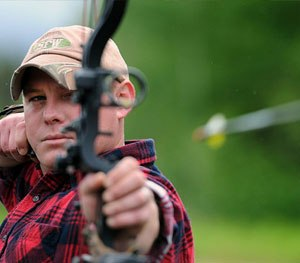 Army Sgt. Josh Leavitt releases an arrow at a target on the base archery range during the 19th annual Military Appreciation Picnic and Arctic Warrior Olympics. (U.S. Air Force photo/Justin Connaher)