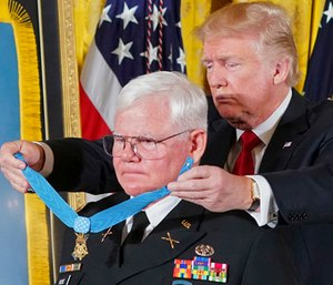 President Donald Trump bestows the nation's highest military honor, the Medal of Honor, to retired Army Capt. Gary M. Rose, during a ceremony in the East Room of the White House in Washington. (AP Photo/Pablo Martinez Monsivais)