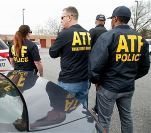 ATF agents gather in a parking lot down the road from Ft. Meade after a vehicle rammed a gate, March 30, 2015. (AP Image)