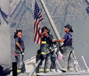 (From l.) Brooklyn firefighters George Johnson, Dan McWilliams and Billy Eisengrein raise a flag at the remains of the World Trade Center on Sept. 11, 2001 in this memorable photo. (Photo/Thomas Franklin/The Record via AP)