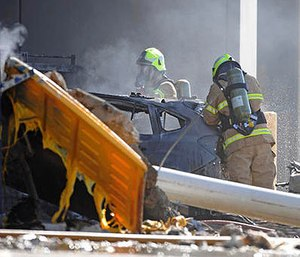 Emergency personnel work at a light plane crashed in Melbourne, Australia, Tuesday, Feb. 21, 2017. The plane crashed into a shopping mall, officials said.