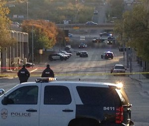 Police tape marks off the scene after authorities shot and killed a man who they say opened fire on the Mexican Consulate, police headquarters and other downtown buildings early Friday, Nov. 28, 2014, in Austin, Texas. In the distance, police cars surround the suspect's vehicle parked near the Interstate 35 overpass.
