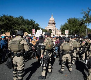 Police in riot gear separate counter-protestors from a White Lives Matter rally outside the Texas State Capitol in Austin, Texas, on Saturday, Nov. 19, 2016. (Dave Creaney/Austin American-Statesman via AP)