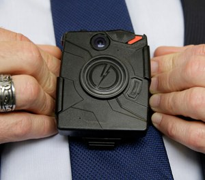 In this Feb. 19, 2015 file photo, Steve Tuttle, vice president of communications for Taser International, demonstrates one of the company's body cameras during a company-sponsored conference at the California Highway Patrol Headquarters in Sacramento, Calif.
