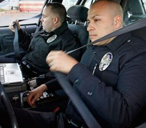 Pictured are L.A.  officers Adrian Garcia, right, and Christopher Ballerini. Studies show leaning forward to type, and exiting your vehicle by pivoting on one knee causes joint and back pain.