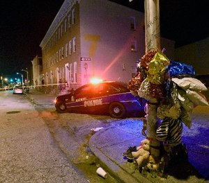 A previously created memorial, right, stands as Baltimore police work at a scene where multiple people were shot in Baltimore, Saturday night, Sept. 24, 2016.