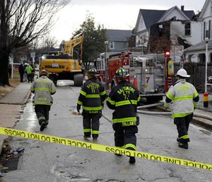 Fire officials approach the scene of an early morning house fire in Baltimore, Thursday, Jan. 12, 2017.