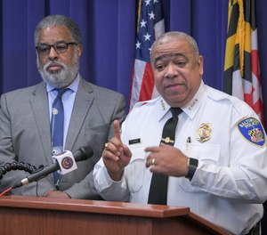 City solicitor Andre Davis, left, listens as Baltimore Police Commissioner Michael Harrison, right, announces support for a pilot program that uses surveillance planes over the city to combat crime on Friday, Dec. 20, 2019, in Baltimore.