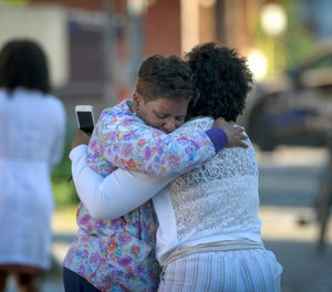 Two women embrace in an alley behind the Man Alive drug treatment center in Baltimore shortly after a shooting. (Jerry Jackson/The Baltimore Sun via AP)