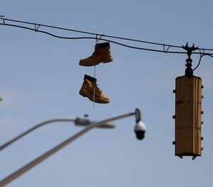In this Wednesday, April 29, 2020 photo, a pair of work boots hang from the wire of a traffic light with a surveillance camera seen in the distance in West Baltimore.