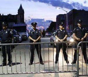 Members of the Baltimore Police Department stand behind barriers outside of the Western District police station during a march for Freddie Gray. (AP Image)