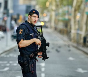 Armed police officers patrol a deserted street in Las Ramblas, in Barcelona, Spain, Friday, Aug. 18, 2017.