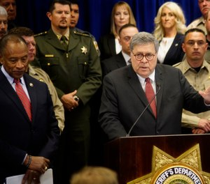U.S. Attorney General William Barr, center, with other federal officials, announces that nearly 330 fugitives suspected of violent crimes have been arrested as part of a crime-fighting initiative in New Mexico. (Photo/AP)