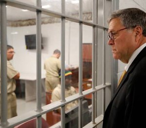 Attorney General William Barr watches as inmates work in a computer class during a tour of a federal prison in Edgefield, S.C. (AP Photo/John Bazemore)