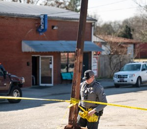 A law enforcement officer removes crime scene tape in front of Mac's Lounge, the scene of an early morning bar shooting, in Hartsville, S.C.
