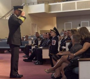 Chief Marc Bashoor salutes the son of a Prince George's County, Maryland, firefighter during the firefighter's funeral.