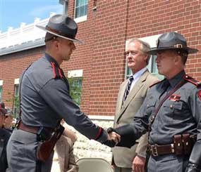 Rhode Island State Trooper Roupen Bastajian, left, shakes the hand of Col. Steven O'Donnell, head of the State Police, as he is awarded the service ribbon, the State Police's highest honor on Thursday, May 16, 2013, in Scituate, R.I.