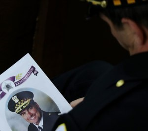 An 18th District officer holds the program for the funeral mass of slain Chicago police Cmdr. Paul Bauer at Nativity of Our Lord Roman Catholic Church in Chicago on February 17, 2017. (Photo/TNS)