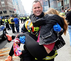Boston firefighter Jimmy Plourde carries injured Victoria McGrath away from the scene after a bombing near the finish line of the Boston Marathon. (Ken McGagh / MetroWest Daily News via AP)