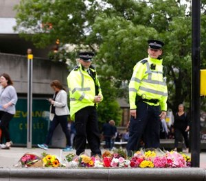 Police officers walk by floral tributes in the London Bridge area of London, Monday, June 5, 2017. (AP Photo/Alastair Grant)