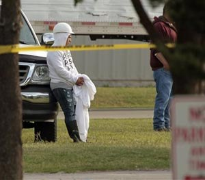 Employees wait in the parking lot as police investigate a shooting at Vaughan Foods on Thursday, Sept. 25, 2014 in Moore, Okla.