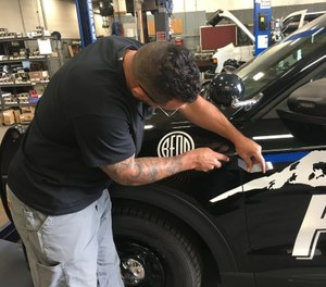 A man removes a thin blue line decal from a Bend Police Department patrol car. (Photo/Bend Police Department)