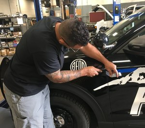 A man removes a thin blue line decal from a Bend Police Department patrol car.