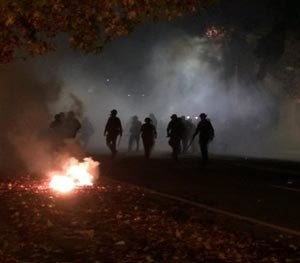 In this photo provided by Tay Nitta, police in riot gear patrol a street in Berkeley, Calif. amid smoke and tear gas after a protest over police killings turned violent, early Sunday, Dec. 7, 2014. (AP Image)