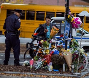 A police officer stands guard as Simon Rubin, 25, arranges flowers at a makeshift memorial to remember the victims of the recent truck attack near the crime scene on Thursday, Nov. 2, 2017, in New York. (AP Photo/Andres Kudacki)