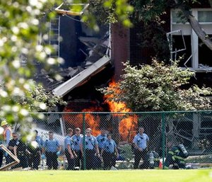 Emergency personnel move away as a gas fire continues to burn following an explosion at Minnehaha Academy. (David Joles/Star Tribune via AP)