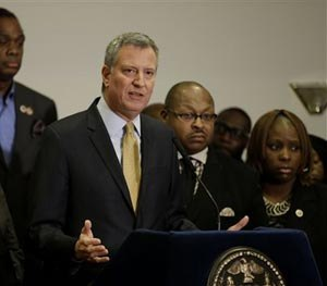 New York City Mayor Bill de Blasio, surrounded by community leaders, speaks to reporters about the grand jury's decision in the Eric Garner case in the borough of Staten Island in New York, Wednesday, Dec. 3, 2014. (AP Image)