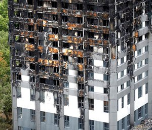 The burnt Grenfell Tower apartment building standing testament to the recent fire in London.