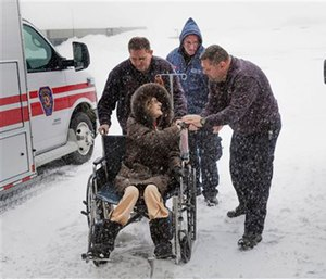 Paramedics wheel a patient into the hospital after driving through a blizzard to reach her.