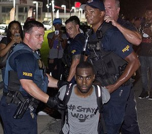 In this July 9, 2016, file photo, police officers arrest DeRay Mckesson for blocking Airline Highway during a protest in Baton Rouge, La.