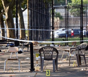 Yellow evidence markers are placed next to chairs at a playground in the Brownsville neighborhood in the Brooklyn borough of New York, Sunday, July 28, 2019. (AP Photo/Mark Lennihan)