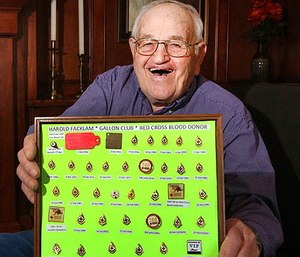 In a March 23, 2017 photo, Harold Facklam displays the many pins he has collected for having donated 32 gallons of blood over more than six decades, in Topeka, Kans. Facklam Jr.