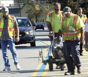 In this Sept. 12, 2016 photo, Wayne, N.J., Department of Public Works employees paint blue line in middle of solid yellow lines on a roadway. (Demitrius Balevski/The Record via AP)
