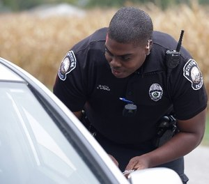In this file photo taken on Tuesday, Sept. 29, 2015, a body camera is attached to the uniform of Whitestown Police Department officer Reggie Thomas during a traffic stop, in Whitestown, Ind.
