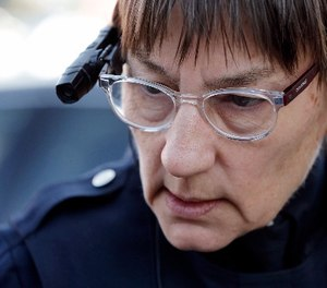 In this Thursday, March 12, 2015, file photo, Seattle police officer Debra Pelich wears a video camera on her eyeglasses, part of a pilot program testing the cameras, as she talks with a local citizen before a small community gathering in Seattle.
