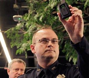 New York Police Department Sgt. Joseph Freer holds a body camera during a news conference while Mayor Bill de Blasio listens.