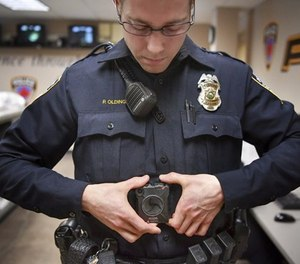 In this Feb. 16, 2017 photo, Maplewood Police Officer Parker Olding attaches his body camera to the magnetic plate worn inside his uniform in Maplewood, Minn.