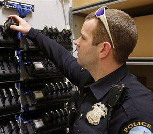 In this Feb. 2, 2015 photo, Duluth, Minn., police officer Dan Merseth demonstrates the docking procedure for police body cameras at police headquarters.